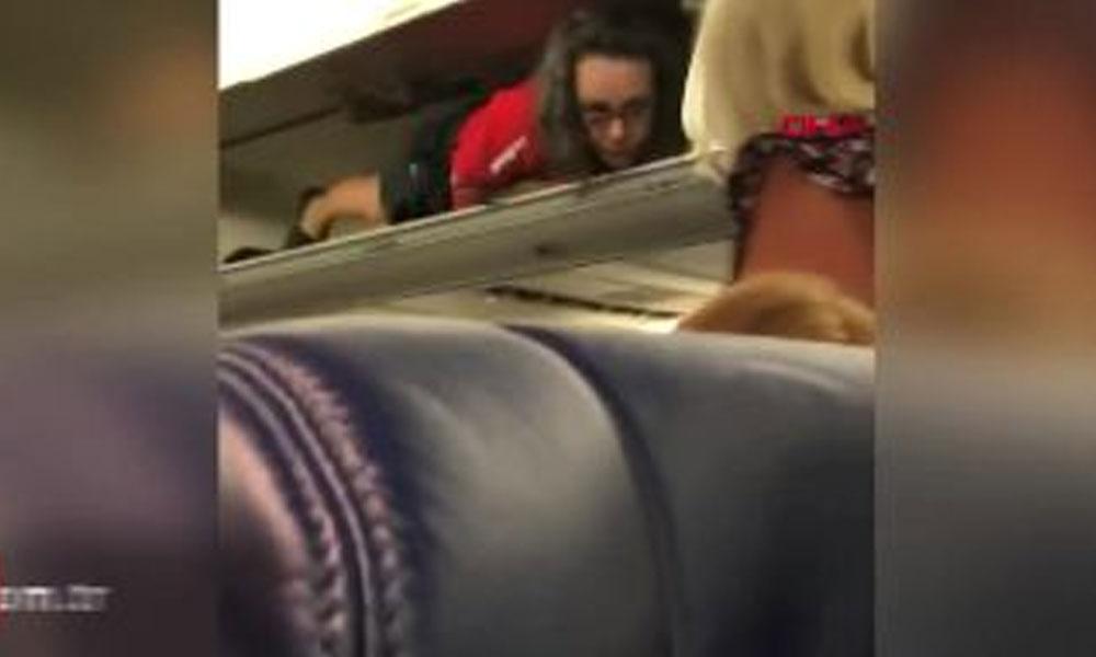 Kabin görevlisi bavul koyulan bölmelere uzandı, yolcularla sohbet etti
