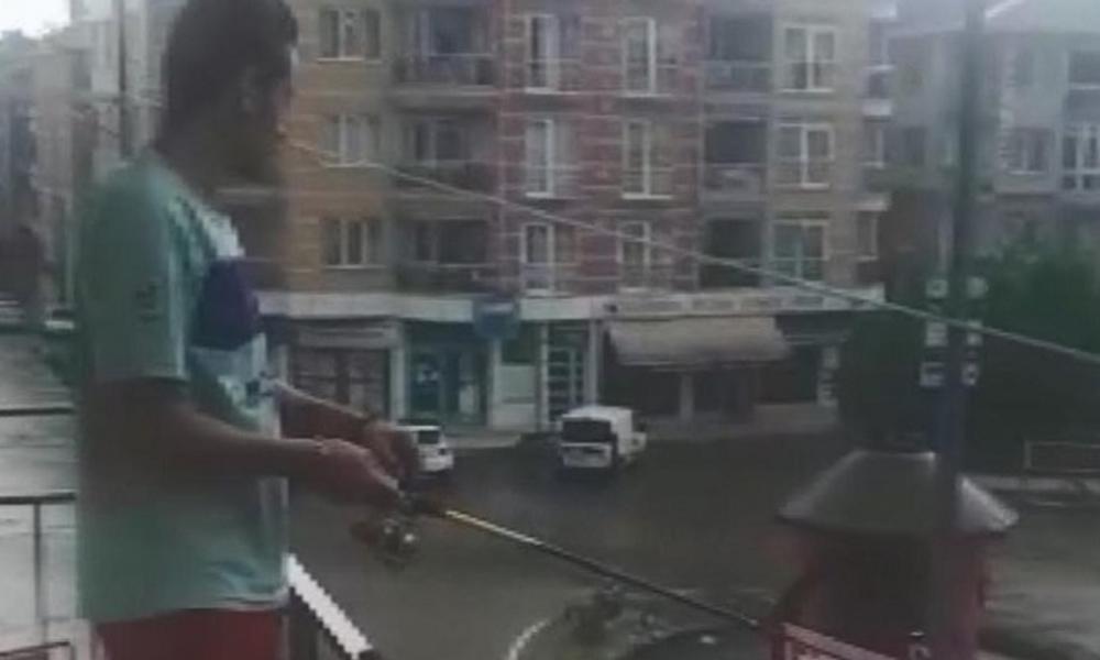 Balkonundan göle dönen caddeye olta attı