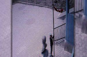 Rüzgarın etkisiyle direğin yarısına inen Türk bayrağını göndere çekti