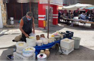 Üç dil bilen rehber, pazarda peynir satıyor